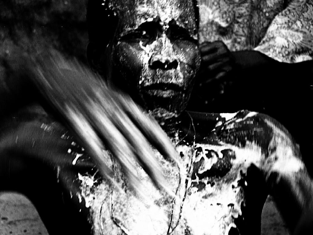 Ein Tänzer bei einer seltenen Regen-Zeremonie am Fluss Mono im Westen Benins im Zustand der Trance. Sein Gesicht ist zum Schutz vor bösen Geistern mit einer Maismaske bedeckt. Wird dem Tänzer der Bastrock übergestreift, werden die brachialen Energien freigesetzt. Sie vereinigen sich mit den Göttern.
