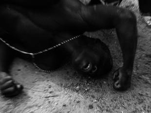 Ein Tänzer im Zustand der Trance während einer seltenen Regen-Zeremonie am Fluss Mono im Westen Benins. Sein Gesicht ist zum Schutz vor bösen Geistern mit einer Maismaske bedeckt. Wird dem Tänzer der Bastrock übergestreift, werden die brachialen Energien freigesetzt. Sie vereinigen sich mit den Göttern. Erschöpft bricht der Voodoosi nach stundenlangem Tanzen zusammen.